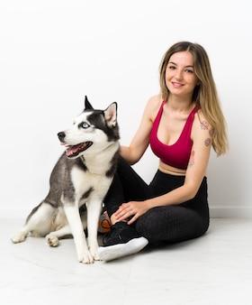 床に座っている彼女の犬を持つ若いスポーツ少女