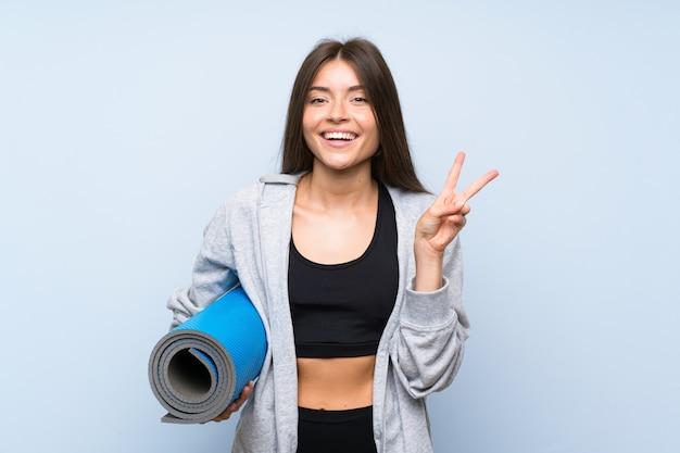 笑顔と勝利のサインを示す分離の青い壁の上のマットを持つ若いスポーツ少女