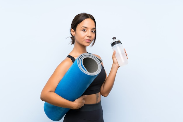 Young sport girl with mat and with a bottle of water over isolated blue