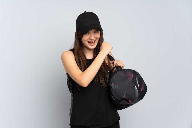 勝利を祝う灰色に分離されたスポーツバッグを持つ若いスポーツの女の子