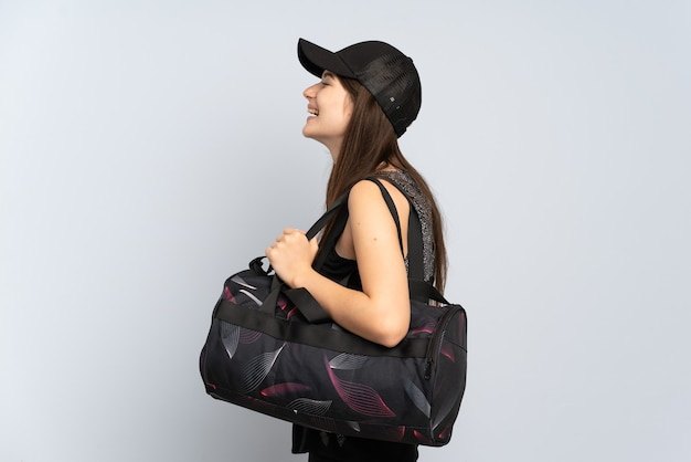 横の位置で笑って灰色で隔離のスポーツバッグを持つ若いスポーツの女の子
