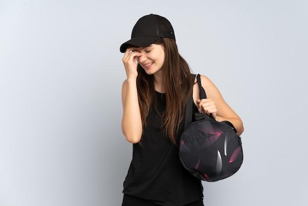灰色の笑いで隔離のスポーツバッグを持つ若いスポーツの女の子