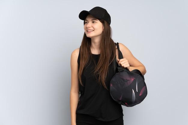 横に見える灰色で隔離のスポーツバッグを持つ若いスポーツの女の子