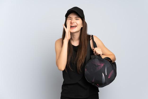 Молодая спортивная девушка со спортивной сумкой изолирована на сером и кричит с широко открытым ртом