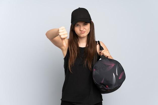 Молодая спортивная девушка со спортивной сумкой, изолированной на сером, показывает палец вниз