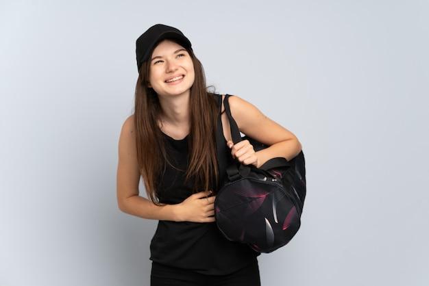 たくさん笑って灰色で隔離のスポーツバッグを持つ若いスポーツの女の子
