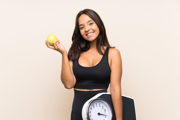 Young sport girl with weighing machine over isolated background