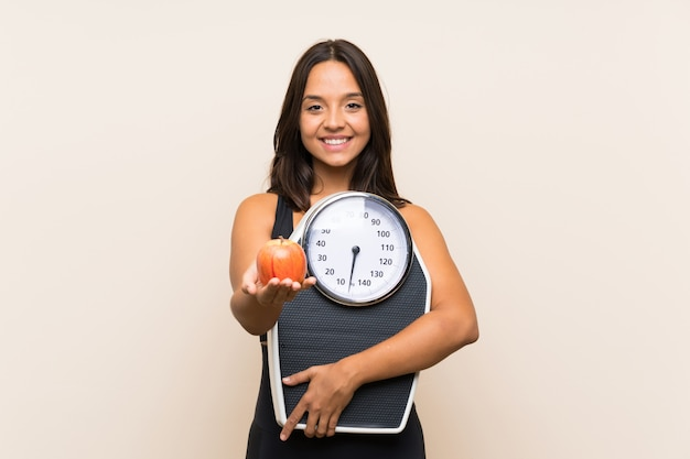 Young sport girl with weighing machine