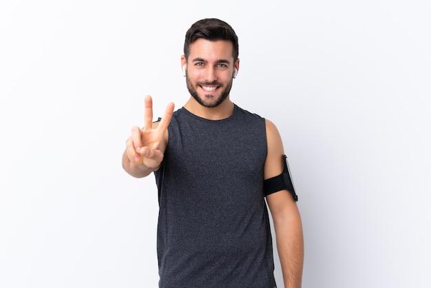 Молодой спортивный красавец с бородой над белым улыбается и показывает знак победы