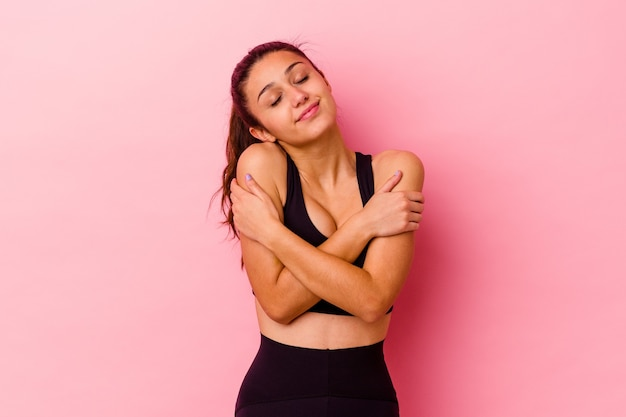 Young sport indian woman isolated on pink wall hugs, smiling carefree and happy