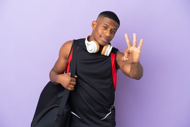 幸せな紫色の壁に分離されたスポーツバッグと指で3を数える若いスポーツラテン男