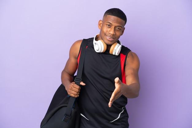 Молодой спортивный латинский мужчина со спортивной сумкой, изолированной на фиолетовой стене, жмет руку для заключения хорошей сделки