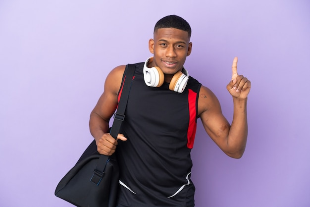 Young sport latin man with sport bag isolated  on purple pointing up a great idea