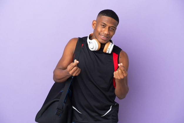 Young sport latin man with sport bag isolated  on purple wall making money gesture