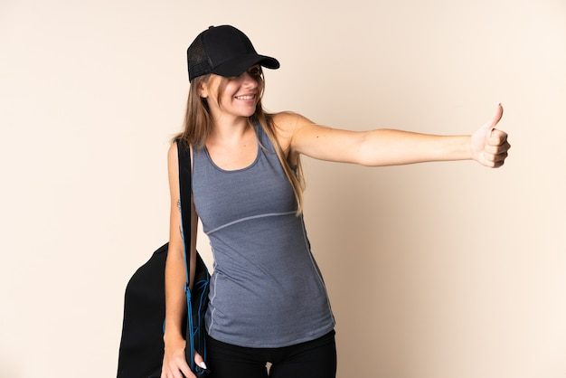 제스처를 엄지 손가락을주는 베이지 색 벽에 고립 된 스포츠 가방을 들고 젊은 스포츠 리투아니아 여자