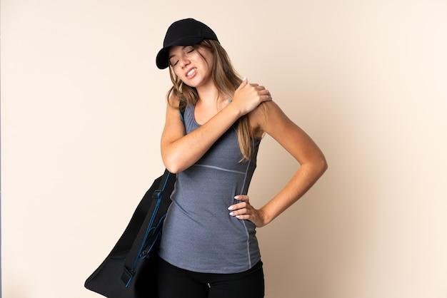 努力したために肩の痛みに苦しんでいるベージュの壁に隔離されたスポーツバッグを保持している若いスポーツリトアニアの女性