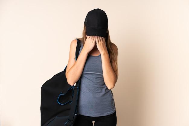 피곤하고 아픈 표정으로 베이지 색에 고립 된 스포츠 가방을 들고 젊은 스포츠 리투아니아 여자