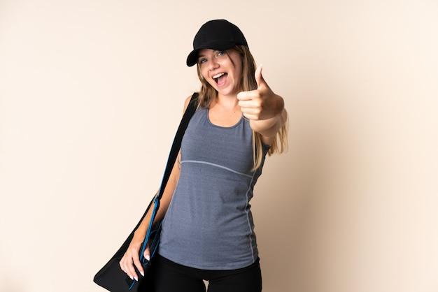 좋은 일이 일어났기 때문에 엄지 손가락으로 베이지 색에 스포츠 가방을 들고 젊은 스포츠 리투아니아 여자