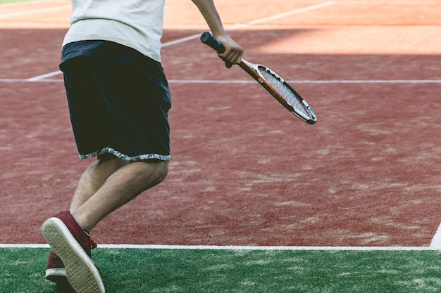 Young sport male tennis player on summer camp practice