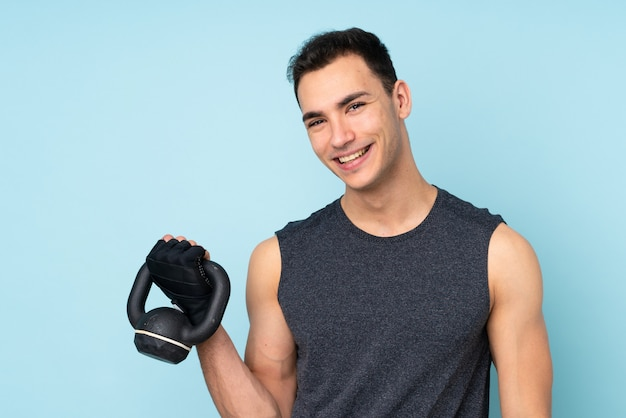Young sport man over on blue wall making weightlifting with kettlebell