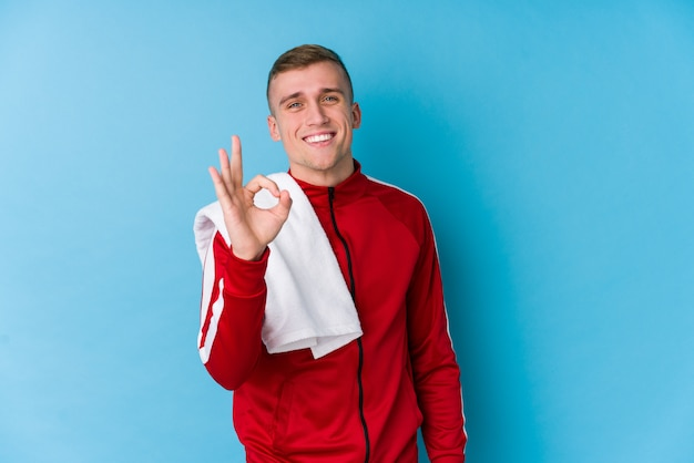 Young sport man cheerful and confident showing ok gesture.