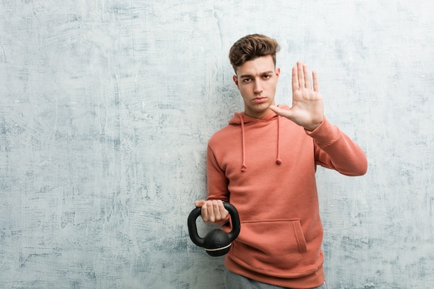 Young sport man holding a dumbbell standing with outstretched hand showing stop sign, preventing you.