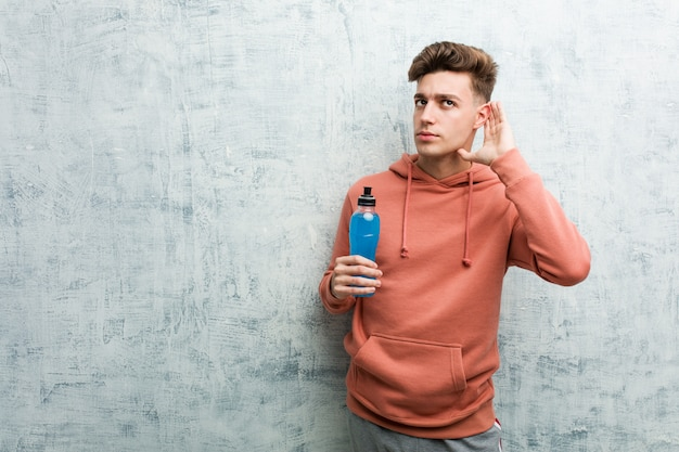 Young sport man holding an energy drink trying to listening a gossip.