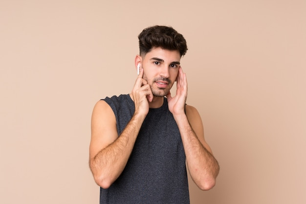 Young sport man over isolated wall listening music