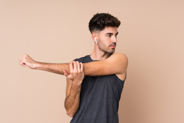 Young sport man over isolated wall stretching arm