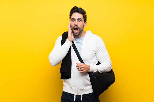 Young sport man over isolated yellow wall with surprise and shocked facial expression