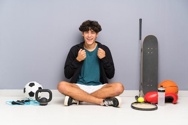 Young sport man sitting on the floor around many sport elements celebrating a victory