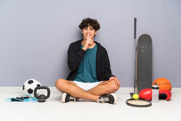 Young sport man sitting on the floor around many sport elements doing silence gesture