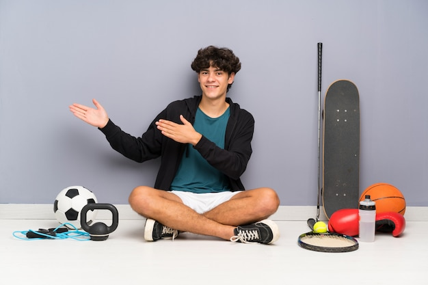 Young sport man sitting on the floor around many sport elements extending hands to the side for inviting to come