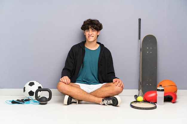 Young sport man sitting on the floor around many sport elements having doubts and with confuse face expression