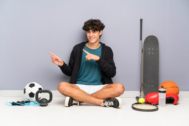Young sport man sitting on the floor around many sport elements pointing finger to the side