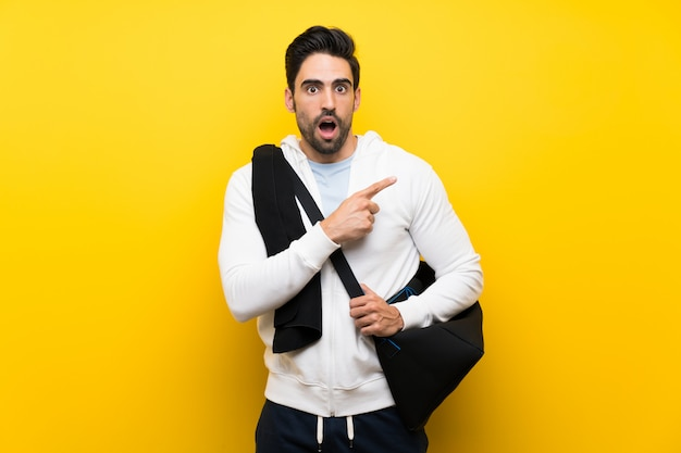 Young sport man surprised and pointing side