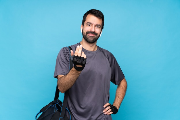 Young sport man with beard inviting to come with hand. happy that you came