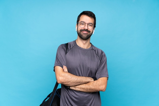 Young sport man with beard over isolated blue wall with glasses and happy