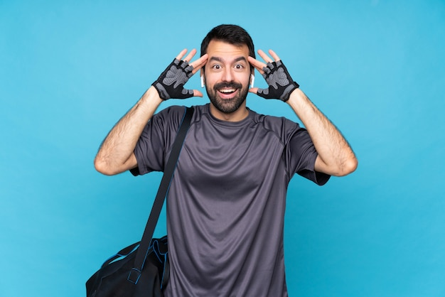 Young sport man with beard over isolated blue wall with surprise expression