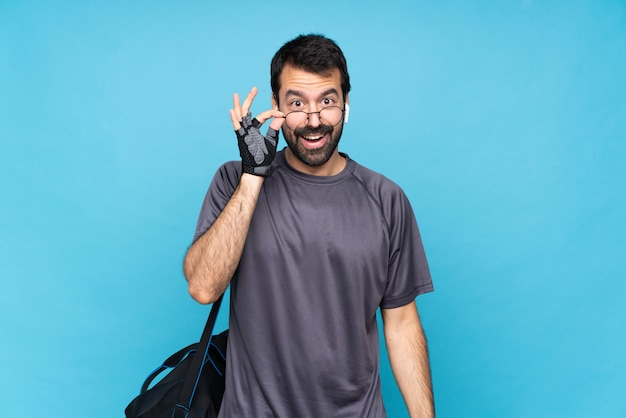 Young sport man with beard over isolated blue  with glasses and surprised