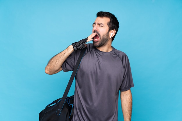 Young sport man with beard over isolated  yawning and covering wide open mouth with hand