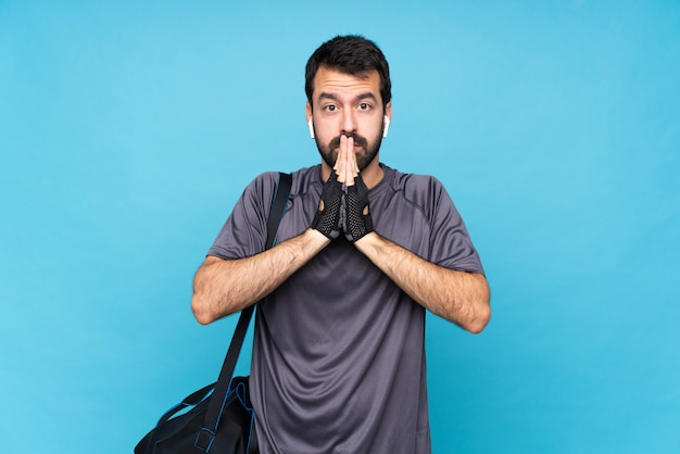 Young sport man with beard keeps palm together