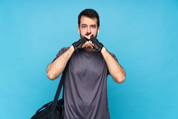 침묵 제스처의 표시를 보여주는 고립 된 파란색 위에 수염을 가진 젊은 스포츠 남자