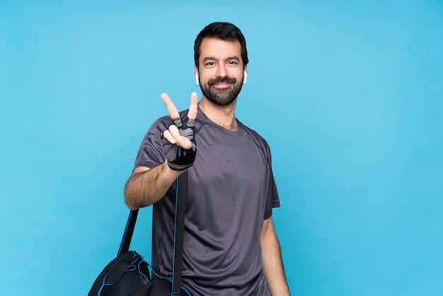 Молодой спортивный человек с бородой над синей улыбкой и показывая знак победы
