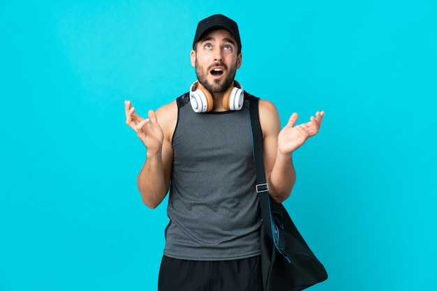Young sport man with sport bag on blue wall stressed overwhelmed
