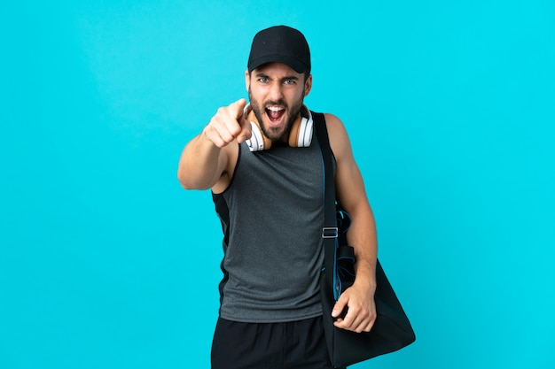 Young sport man with sport bag isolated on blue wall frustrated and pointing to the front