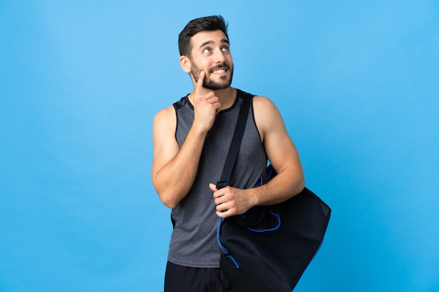 Young sport man with sport bag isolated on blue wall thinking an idea while looking up