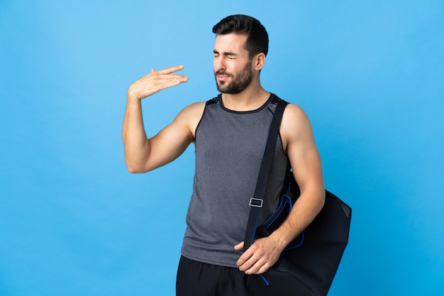 Young sport man with sport bag isolated on blue wall with tired and sick expression