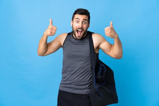 제스처를 엄지 손가락을주는 파란색 배경에 고립 된 스포츠 가방 젊은 스포츠 남자