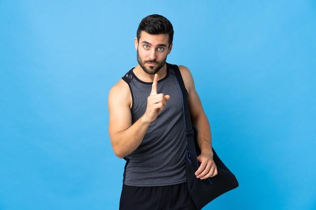 Молодой спортивный человек со спортивной сумкой, изолированной на синем, разочарован и указывает вперед